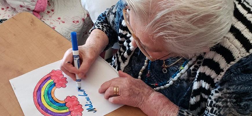 Personne âgée qui dessine un arc-en-ciel